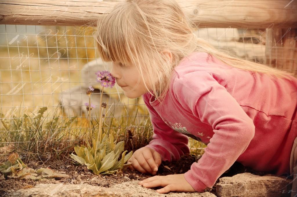 Aromaterapia y propiedades aceites esenciales. Imagen niña oliendo una flor