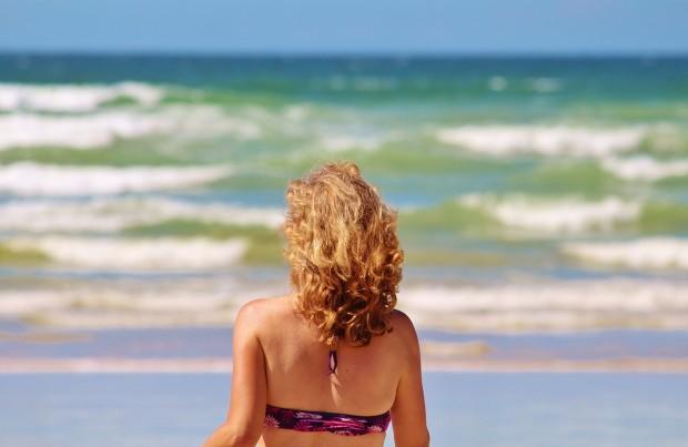 Aceites vegetales para la piel, mujer rubia en la playa, notas naturales