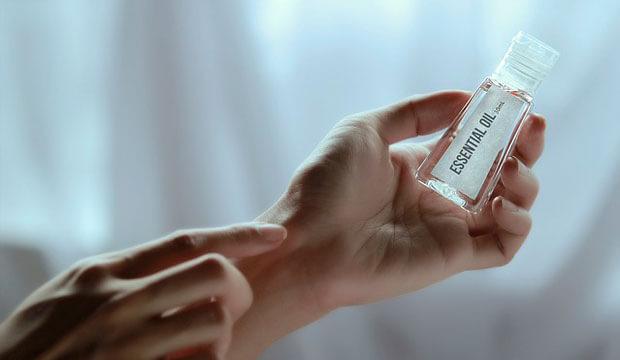 manos de mujer sujetando un frasco de aceite esencial