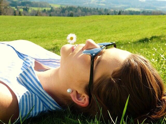 mujer tumbada en un parque como técnica de relajación contra el bruxismo