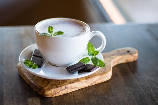 taza de capuccino decorada con hojas de menta y chocolate