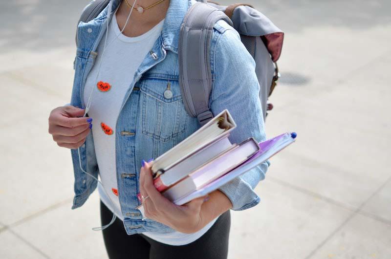 chica estudiante de fitoterapia en la calle sujeta libros