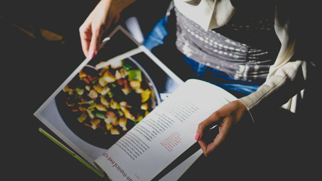 Mujere leyendo un libro de hierbas aromáticas y especias para cocina