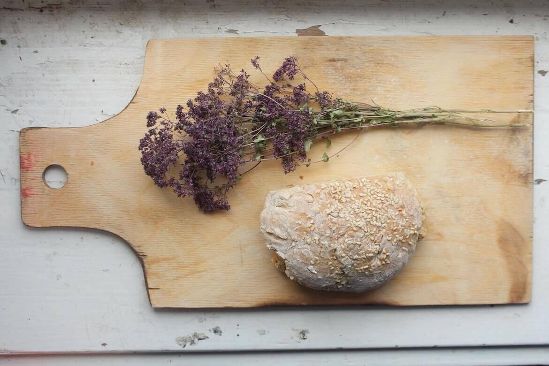 Tabla de madera con pan y hierbas aromáticas secas