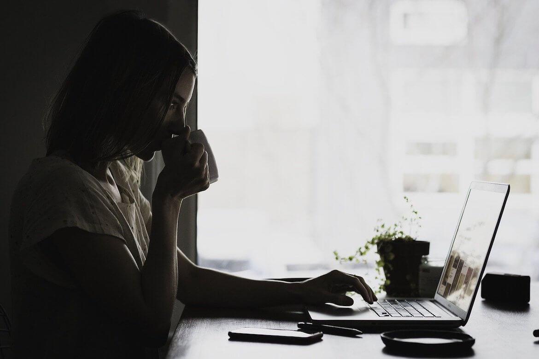 mujer relajada lee revista de fitoterapia online en su ordenador