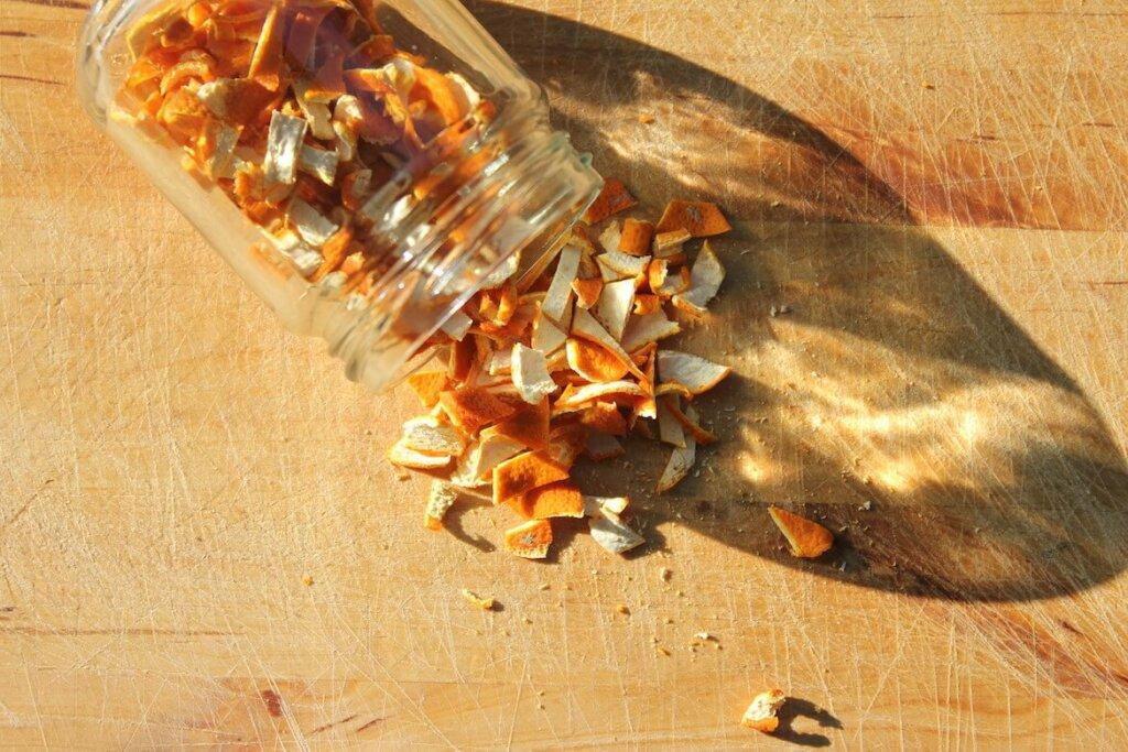 frasco con trozos de cáscara de naranja deshidratada