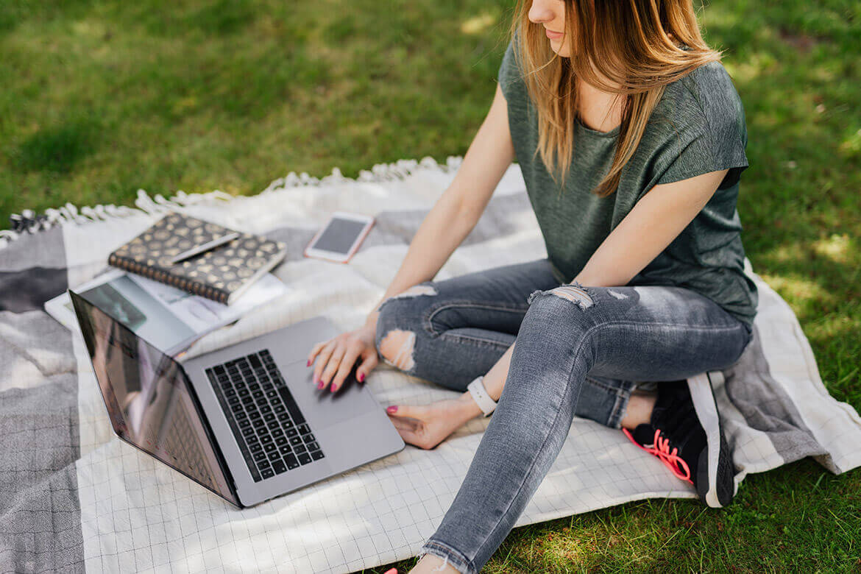 Mujer sentada en un césped lee en su ordenador informaciones sobre qué es un producto reacondicionado