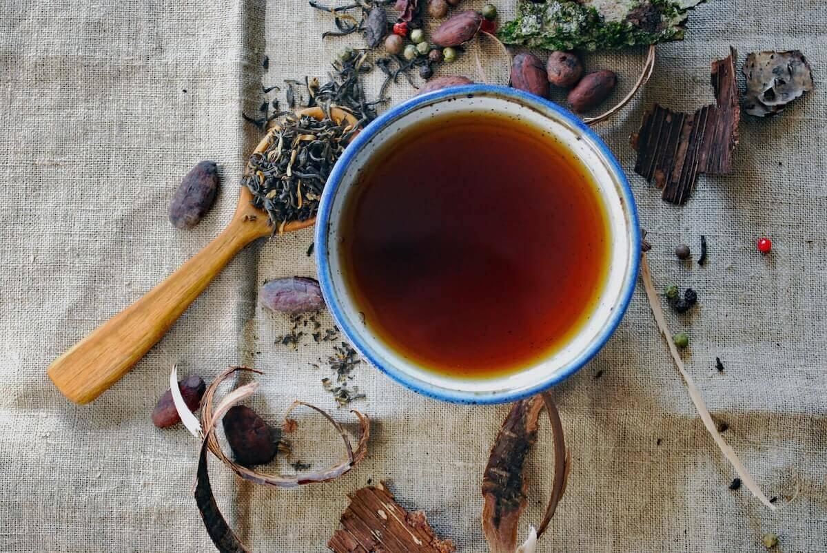taza de infusión y hierbas a granel en una mesa