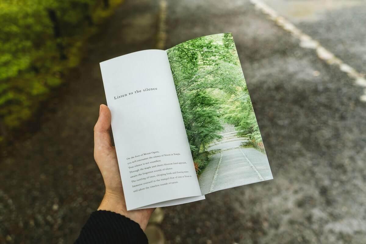 mano de un hombre sujeta un libro sobre naturaleza