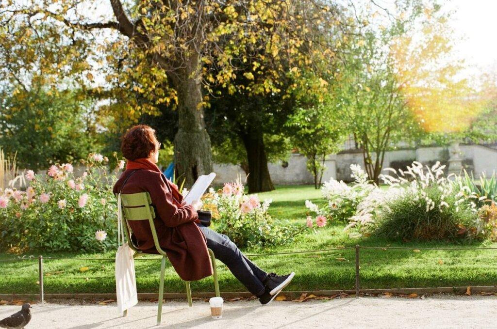 una mujer amante de la naturaleza lee sentada en un parque entre flores