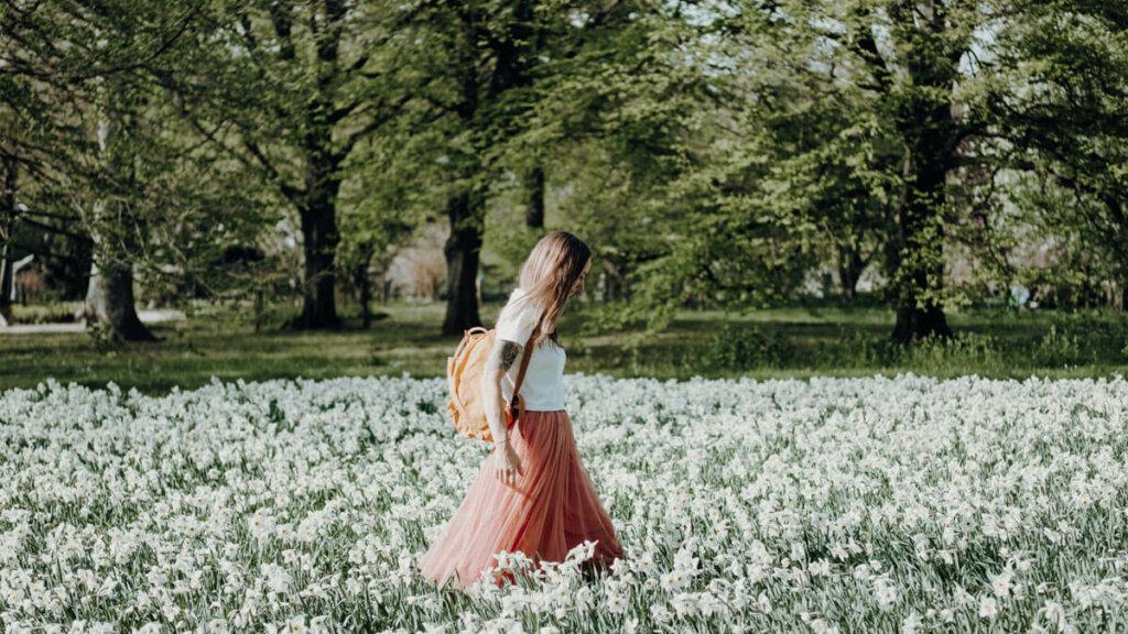 mujer pasea por el campo entre flores